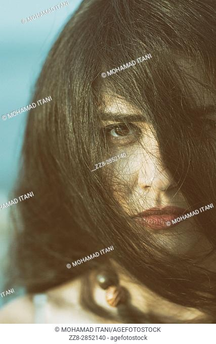 Close up portrait of a sad young woman hair covering face
