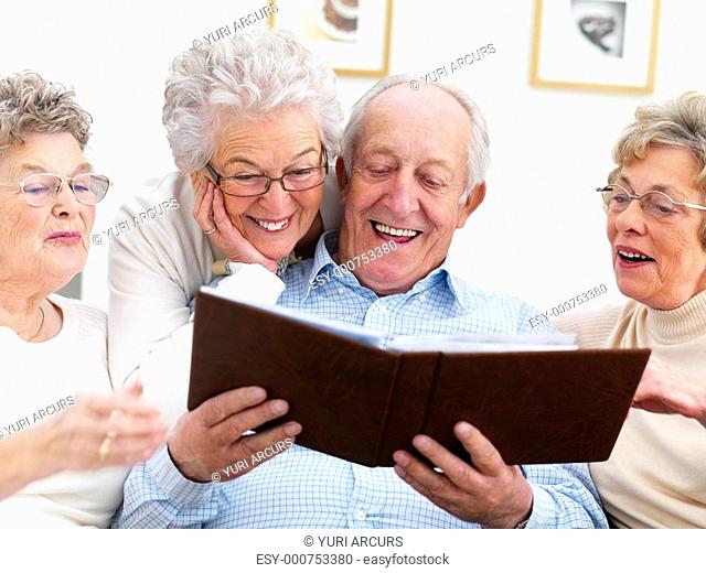 A group of smiling senior people viewing an album