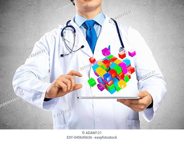 Young and successful doctor in medical suit showing set of multiple cubes above tablet in his hands while standing against white background