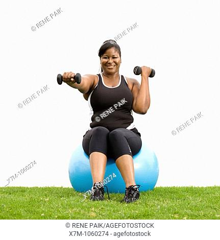 Plus size model working out with weights on cardio ball