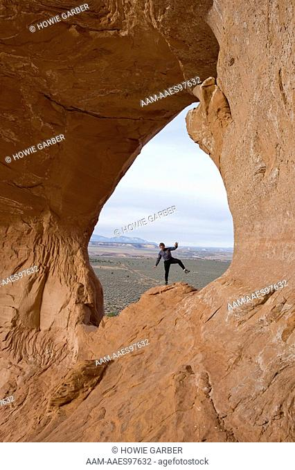 Dave Medera, climbing guide with Moab Desert Adventures, balances on Looking Glass Rock, near Moab, Utah, Model released, MR