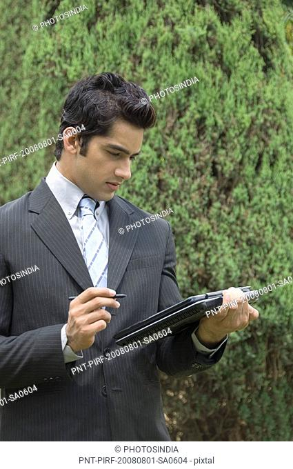 Businessman holding a laptop in a park