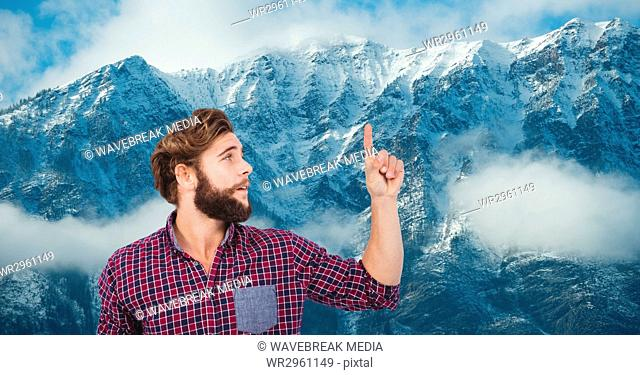 Male hipster pointing against snow covered mountains