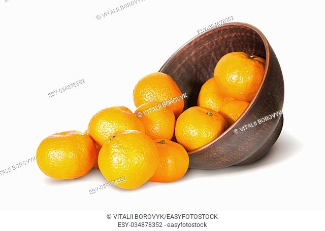 Tangerines Spill Out Of Clay Bowl Isolated On White Background