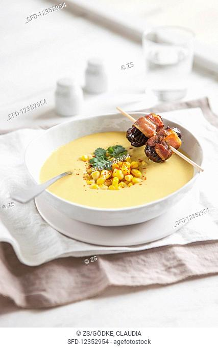 A bowl of creamy corn soup garnished with a date and bacon skewer