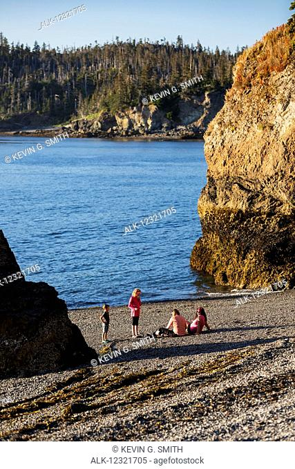Two mothers and their children relax on the beach on Hesketh Island, Southcentral Alaska, USA
