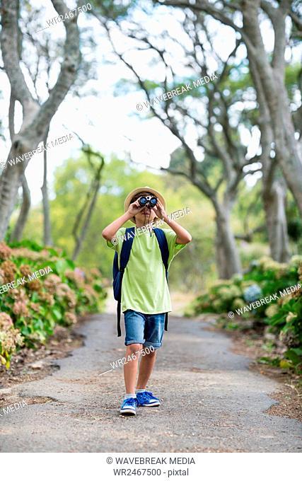 Young boy looking through binoculars in park