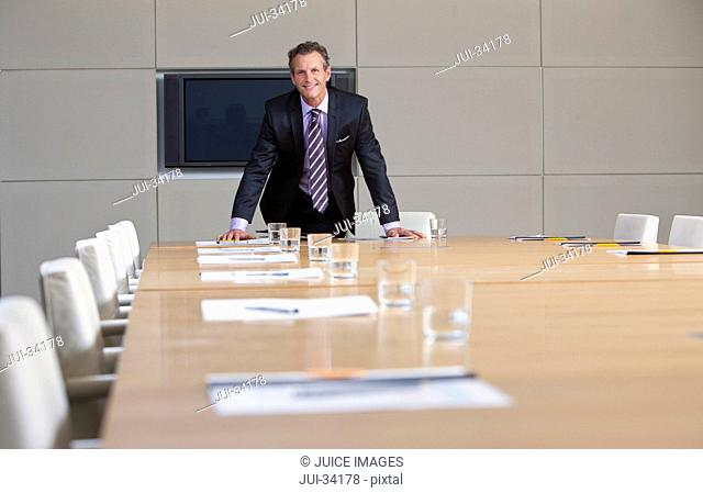 Portrait of smiling businessman leaning on table in conference room