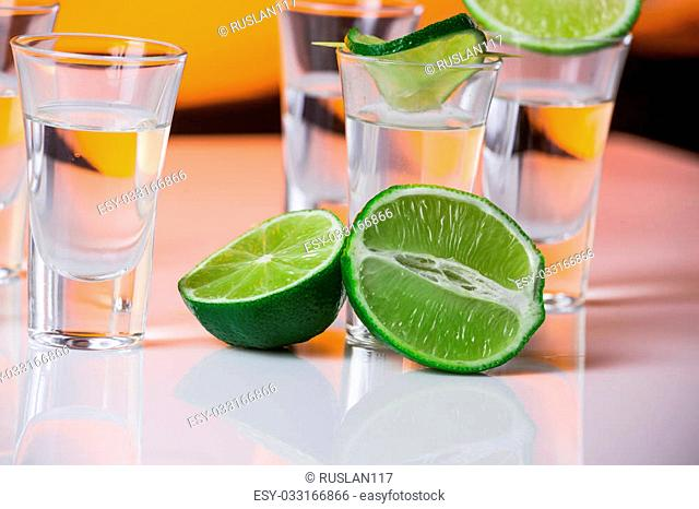 Tequila shot with a slice of lime on the glass on orange background. Selective Focus