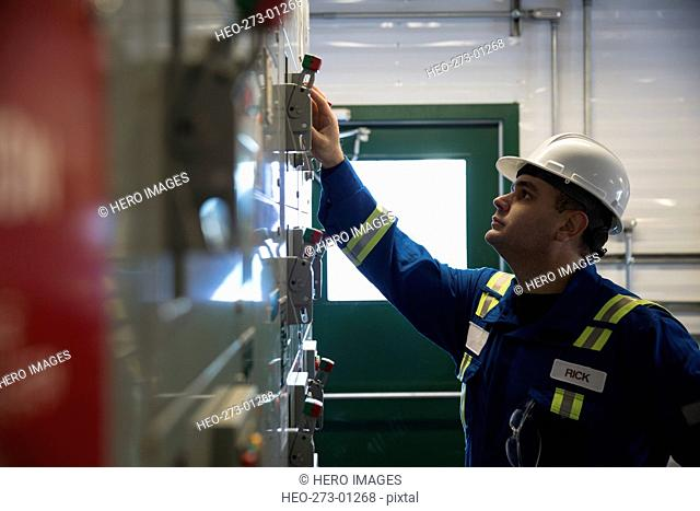 Male worker at control panel in gas plant
