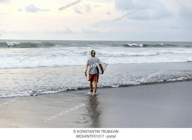 Indonesia, Bali, surfer walking into water