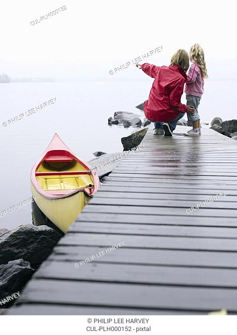 Woman and young girl on a dock near a boat pointing