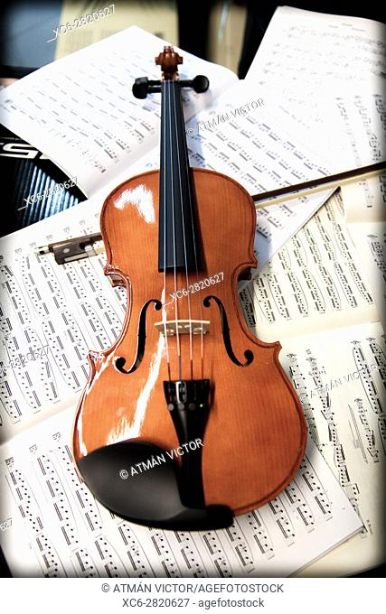 violin laying on sheets of music