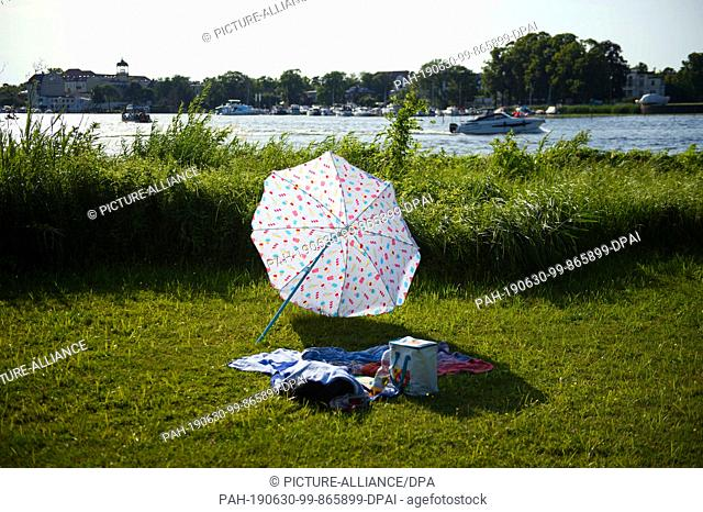 30 June 2019, Brandenburg, Potsdam: A parasol lies next to a blanket and personal items on a meadow on the shore of the Deep Lake