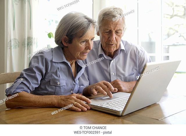 Germany, Bavaria, Senior couple using laptop at home