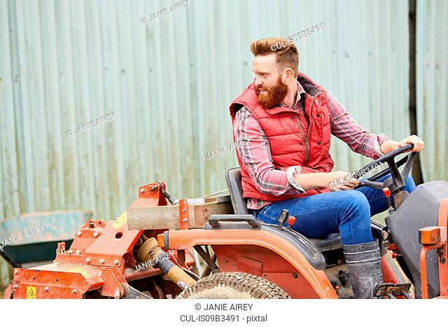 Man on farm driving tractor