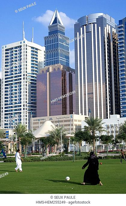 United Arab Emirates, Dubai, the rare case of a woman playing football with the towers of Sheikh Zayed Road in the background