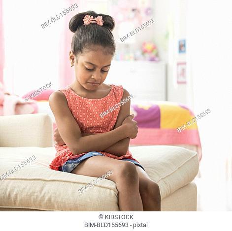 Pouting Hispanic girl sitting on sofa
