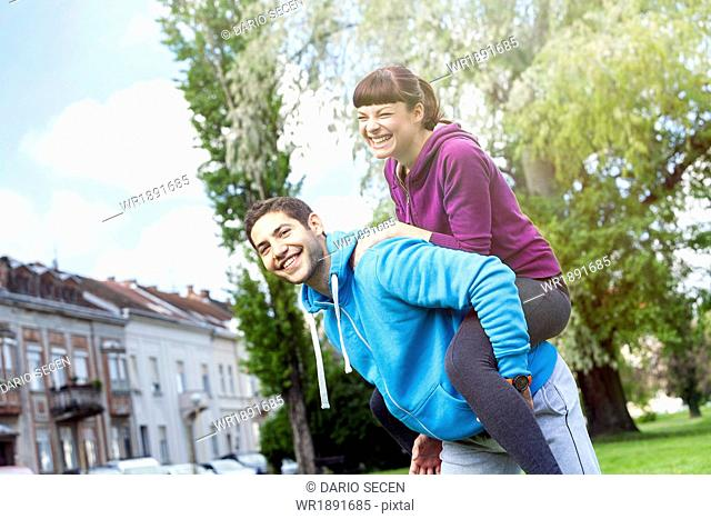 Young man carrying girlfriend piggyback, Osijek, Croatia