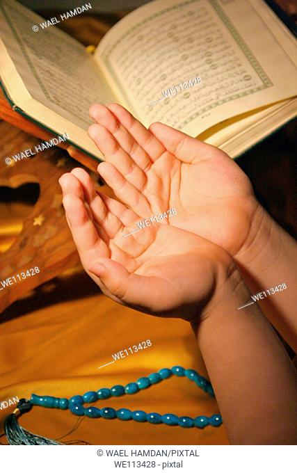 young girl pray with Koran book