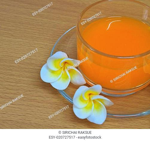 orange juice with flowers on wooden table
