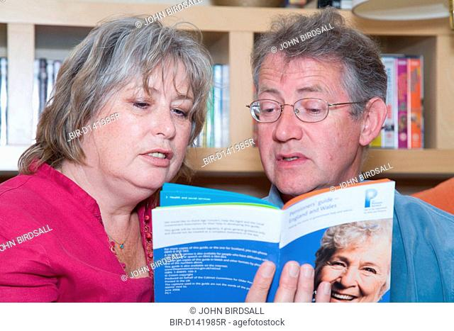 Middle aged couple planning for retirement reading leaflets giving pension advice