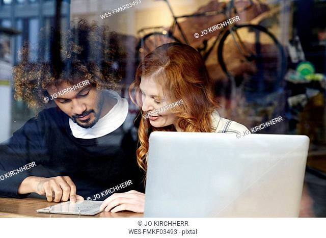 Young couple with laptop and menu behind windowpane