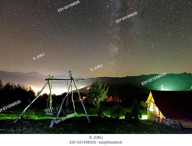 Milky Way galaxy in starry night sky and rural yard illuminated in green color on mountain hill