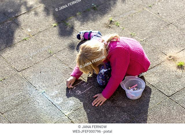 Blond little girl drawing with crayons on pavement