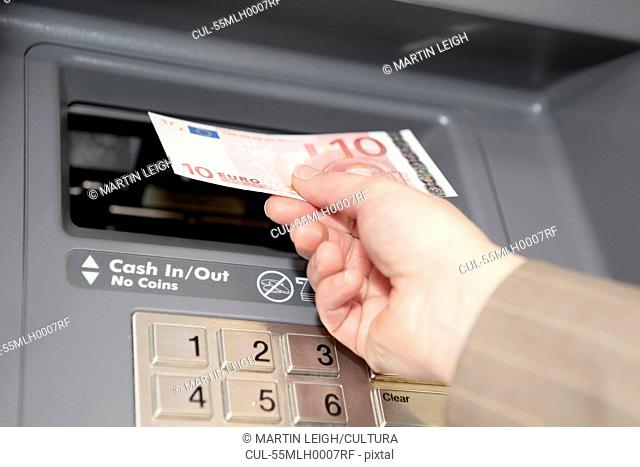 Woman withdrawing ten euro note from cashpoint