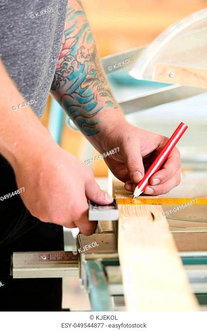 Craftsman measures length of a wooden plank. Makes a line with a pencil before sawing