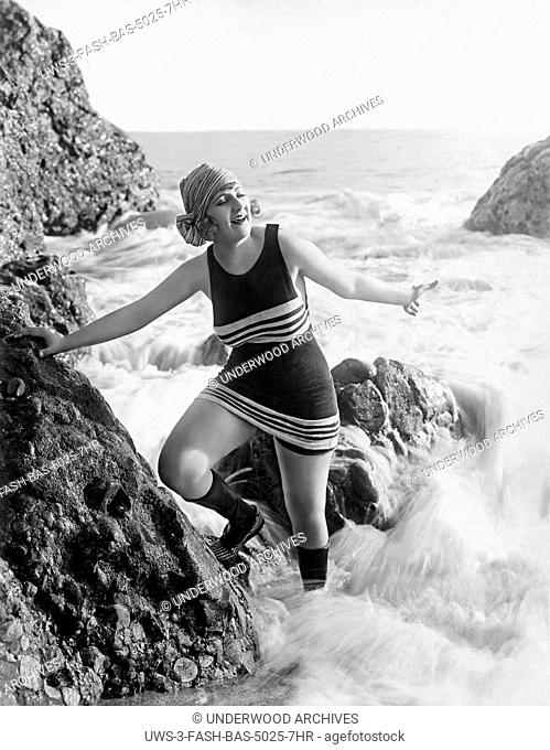 Los Angeles, California: c. 1922.A flapper in a bathing suit, scarf, and footwear plays in the surf on a rock at the beach
