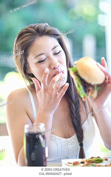 Young woman enjoying a burger