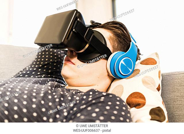 Young man with 3D Glasses lying on the couich at home