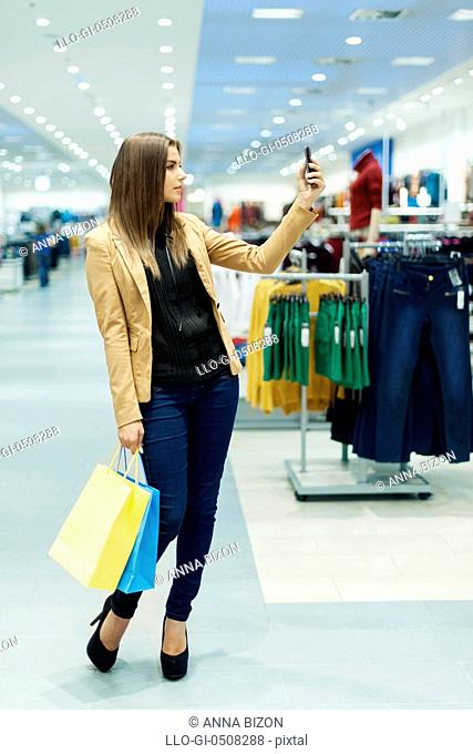Young woman with shopping bags and mobile phone, Debica, Poland