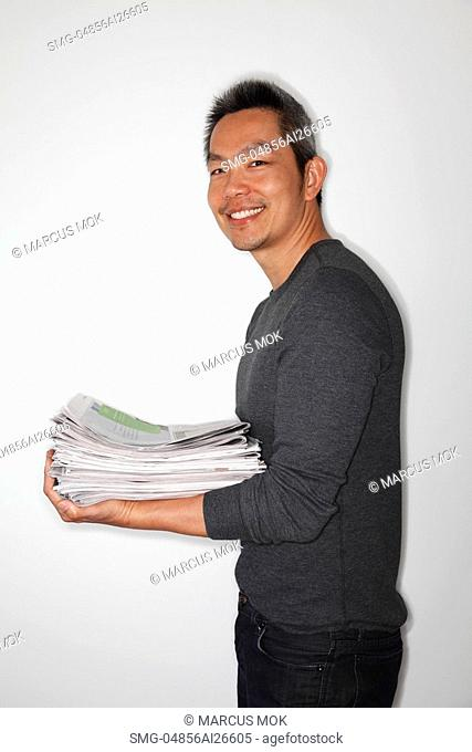 Chinese man holding newspapers ready to recycle