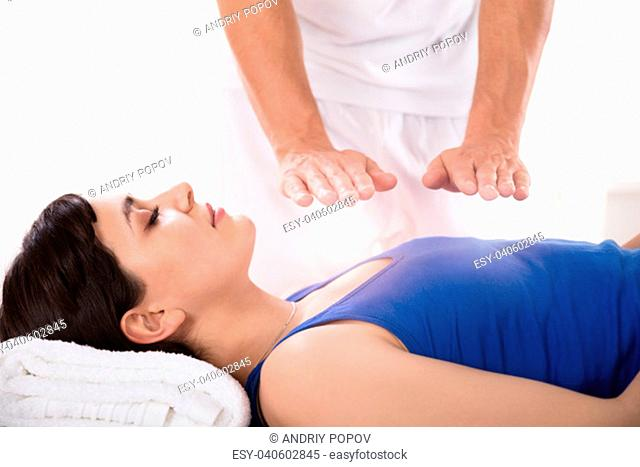 Close-up Of A Relaxed Young Woman Having Reiki Healing Treatment