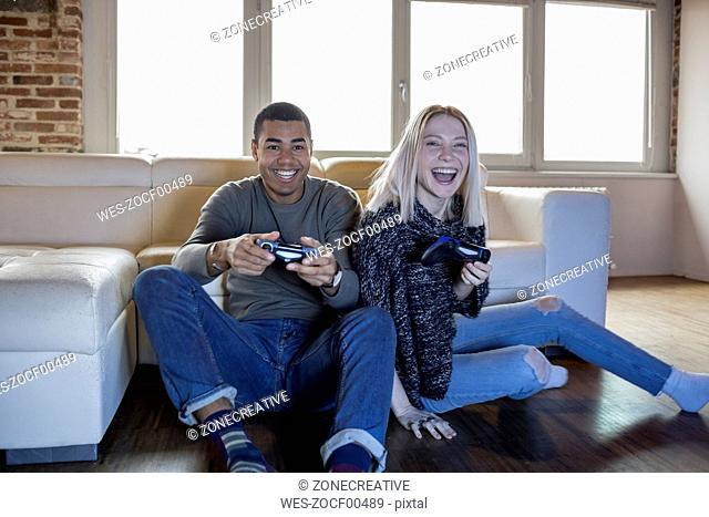 Two friends playing computer game at home