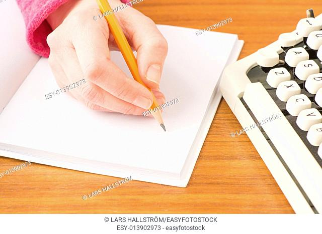 Woman writing in notebook. Conceptual image of office work or education