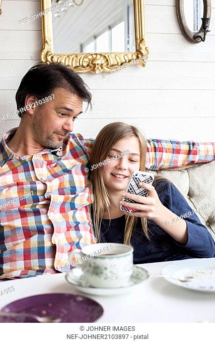Girl with father looking at phone