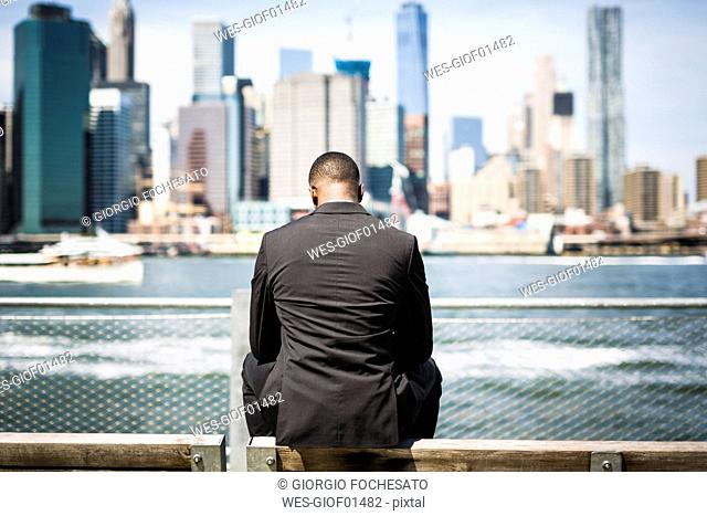 USA, Brooklyn, back view of businessman sitting on bench in front of Manhattan skyline