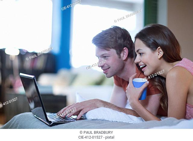 Couple using laptop together on bed