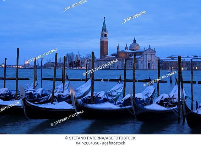 Snow covered gondolas at dawn, San Giorgio Maggiore, Venice, Italy