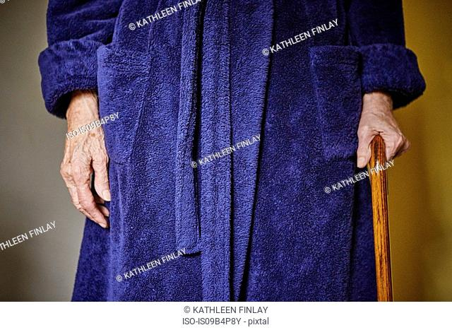 Senior woman standing with walking cane, mid section