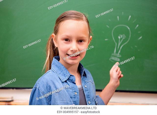 Smiling schoolgirl pointing at a bulb