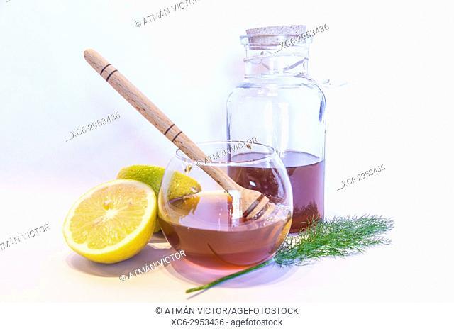 stil life with honey wooden spoon, sliced lemon and honey jar