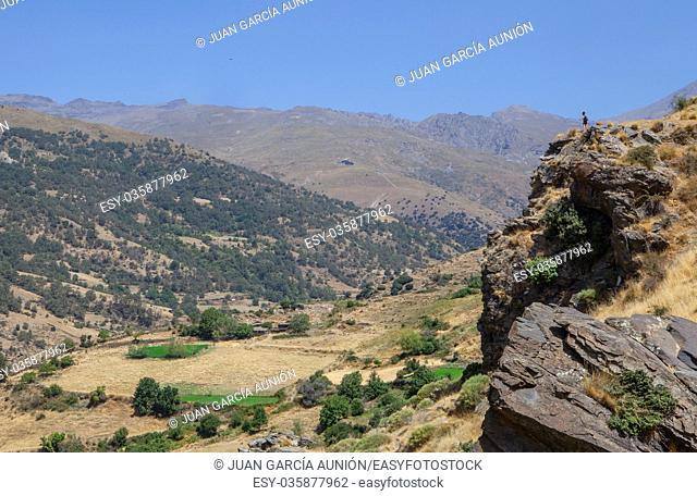 Hiker woman walking along Poqueira Gorge. Las Alpujarras Region, Granada, Spain