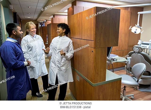 Dentists talking in office corridor