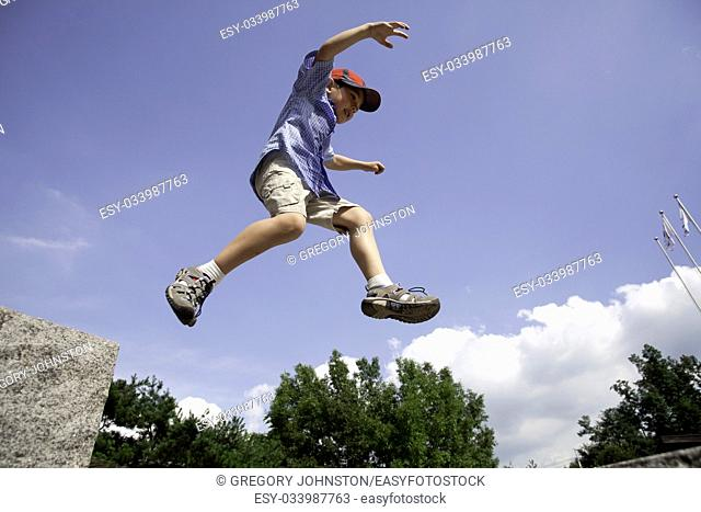 A young boy leaps off a large rock and is in mid air against the blue sky