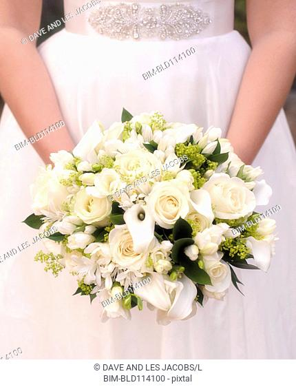 Caucasian bride holding bouquet of white flowers